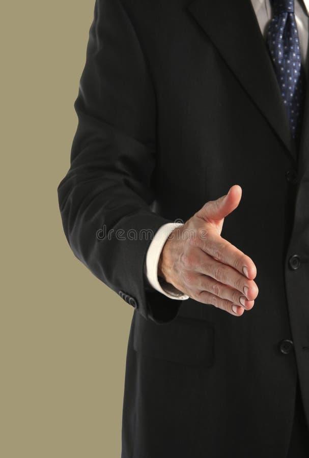 Homem no terno que alcanga para agitar as mãos foto de stock royalty free