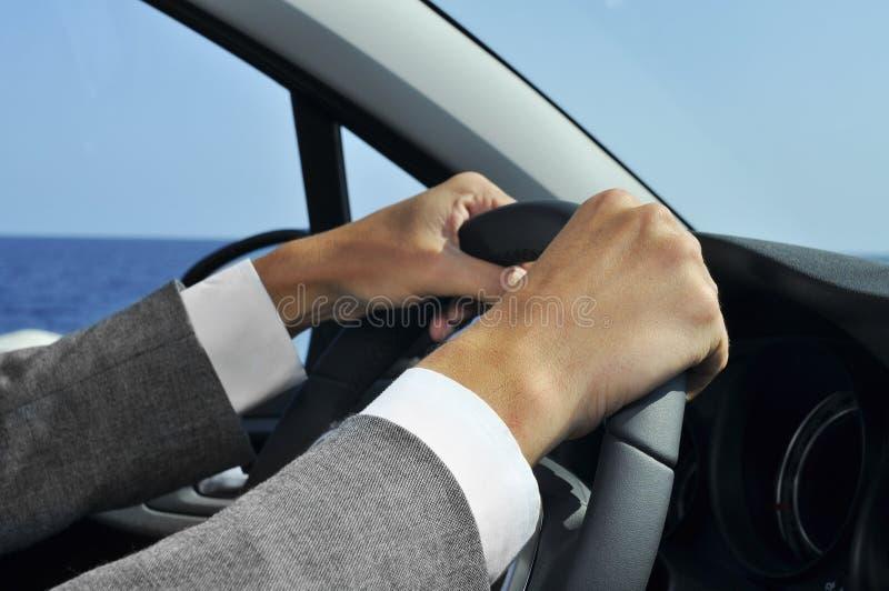Homem no terno que conduz um carro foto de stock