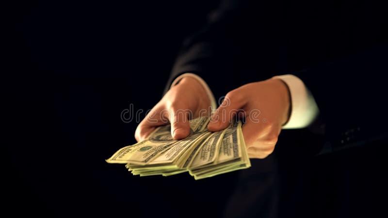 Homem no terno que conta o dinheiro contra o fundo escuro, neg?cio de neg?cio ilegal foto de stock royalty free