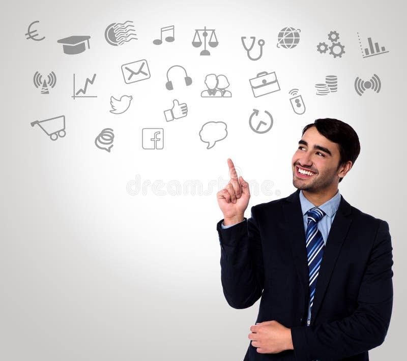 Homem no terno que escolhe ícones da tecnologia imagem de stock