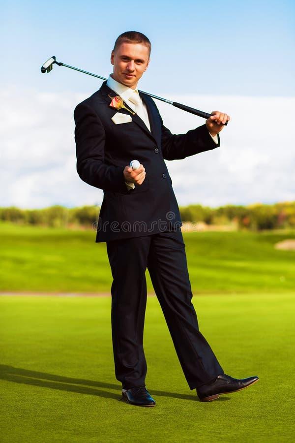 Homem no terno que guarda a bola e a madeira do golfe fotografia de stock