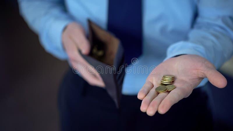 Homem no terno que guarda moedas na palma aberta, dando doações, rendimentos reduzidos, pobreza fotos de stock