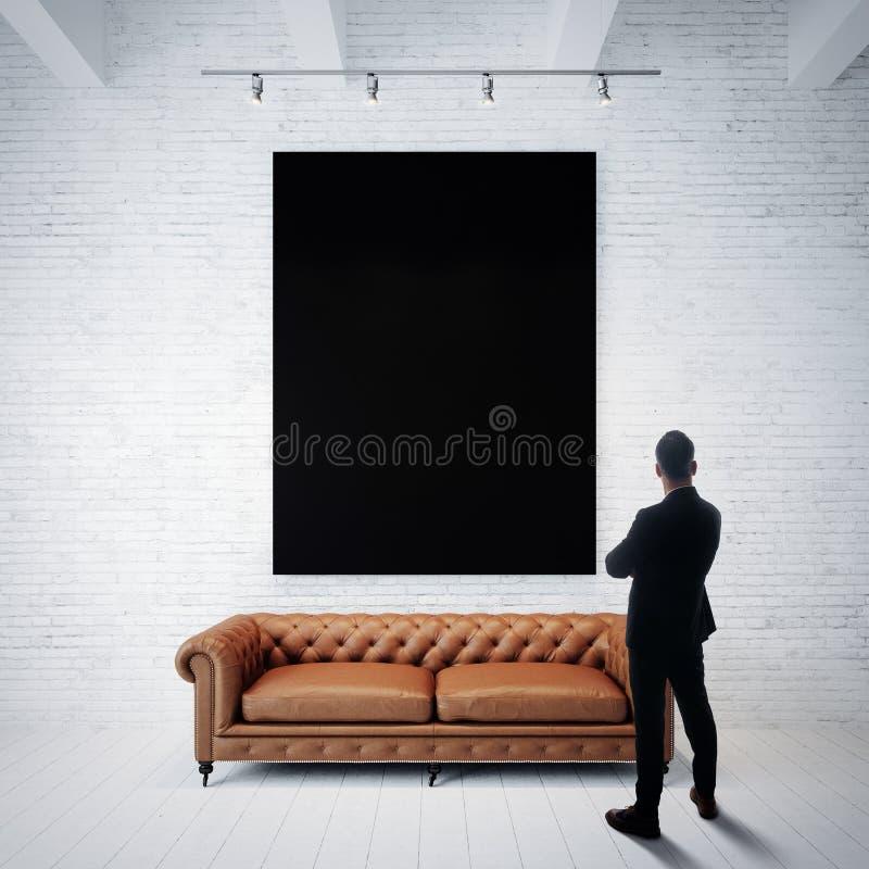 Homem no terno que olha o cartaz preto que guarda sobre a parede de tijolo branca Sofá clássico, assoalho de madeira vertical fotografia de stock