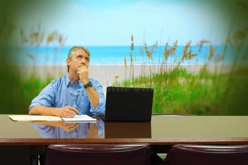 Homem no trabalho que sonha acordado sobre férias calmas bonitas da praia foto de stock