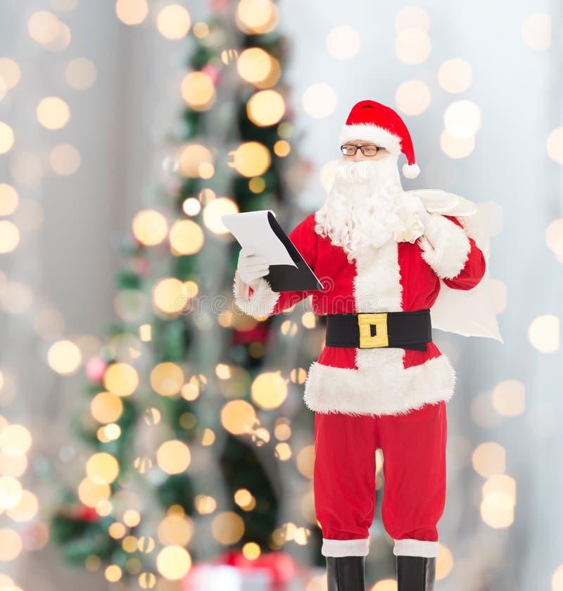 Homem no traje de Papai Noel com bloco de notas e saco imagem de stock royalty free