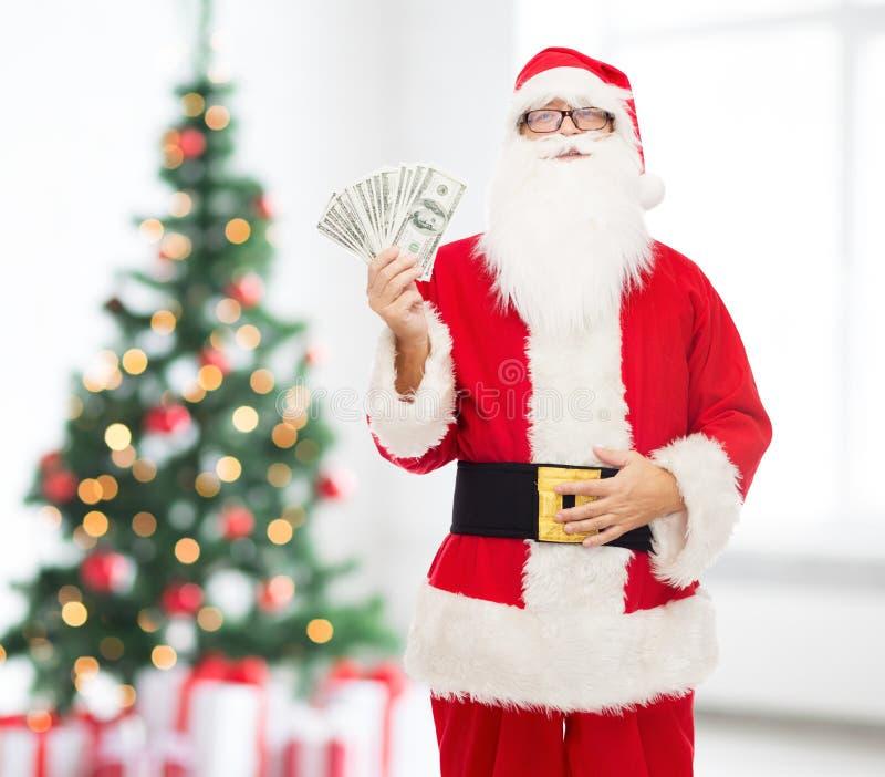 Homem no traje de Papai Noel com dinheiro do dólar fotos de stock royalty free