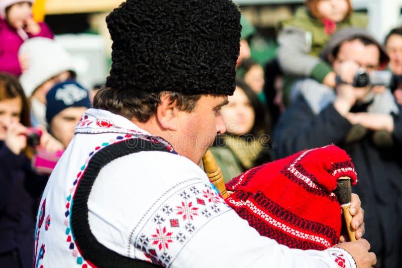 Homem no traje tradicional romeno, jogando a tubulação foto de stock