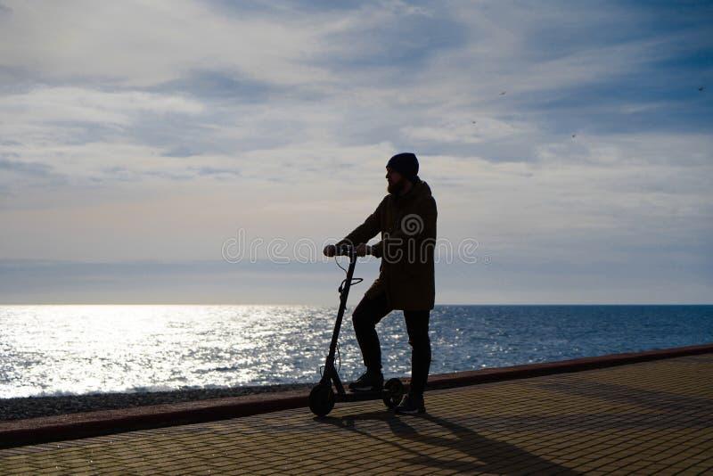 Homem no 'trotinette' no por do sol, silhueta, espa?o livre imagem de stock royalty free