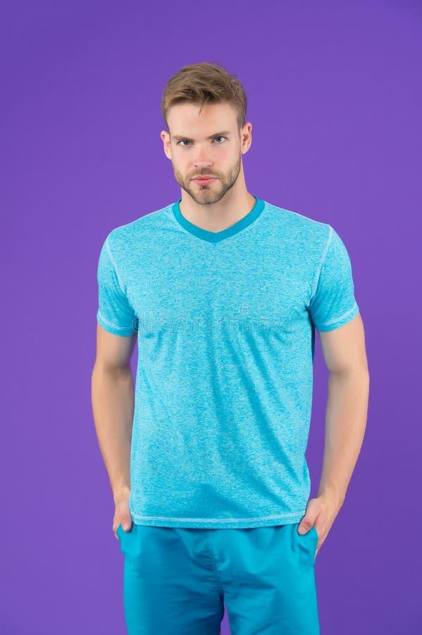 Homem no tshirt e short no fundo violeta Indivíduo na roupa ocasional azul Macho no desgaste ativo para o exercício ou no treinam fotografia de stock royalty free