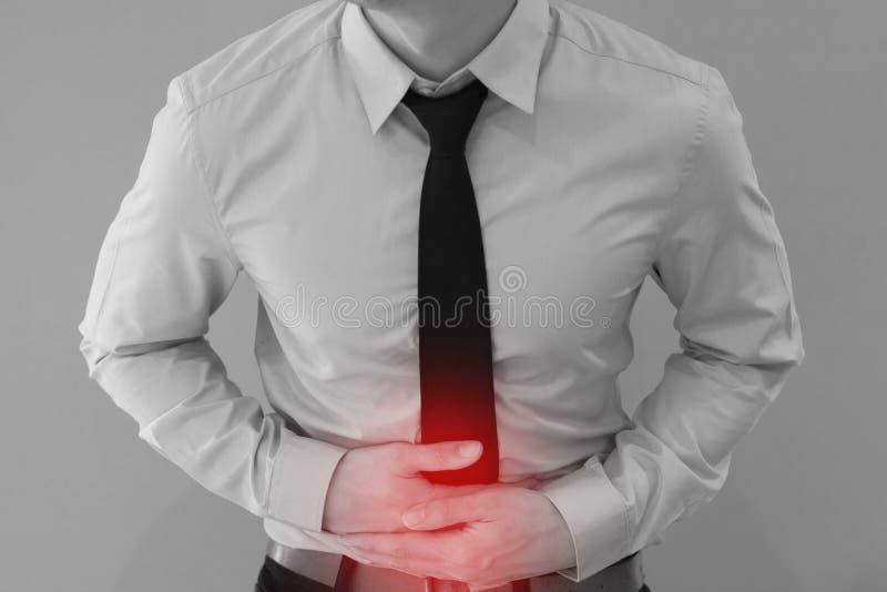 Homem no uniforme do escritório que tem uma dor de estômago/problemas da intoxicação alimentar/estômago imagem de stock royalty free