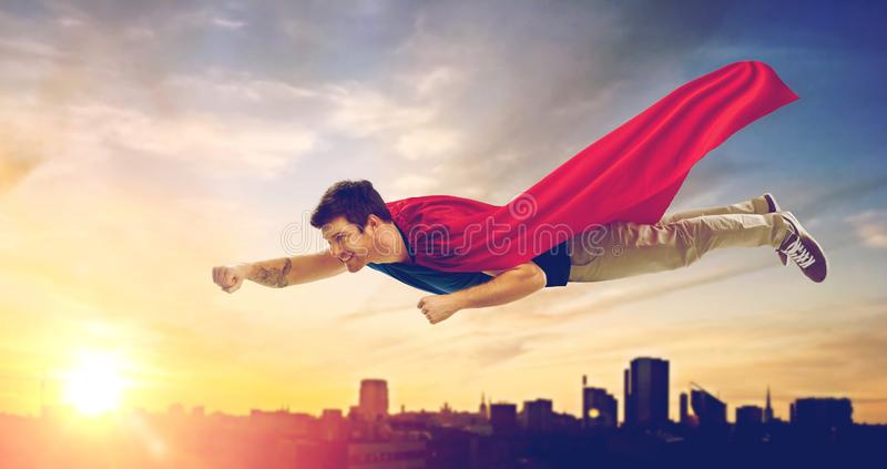 Homem no voo do cabo do super-herói sobre o por do sol na cidade fotos de stock