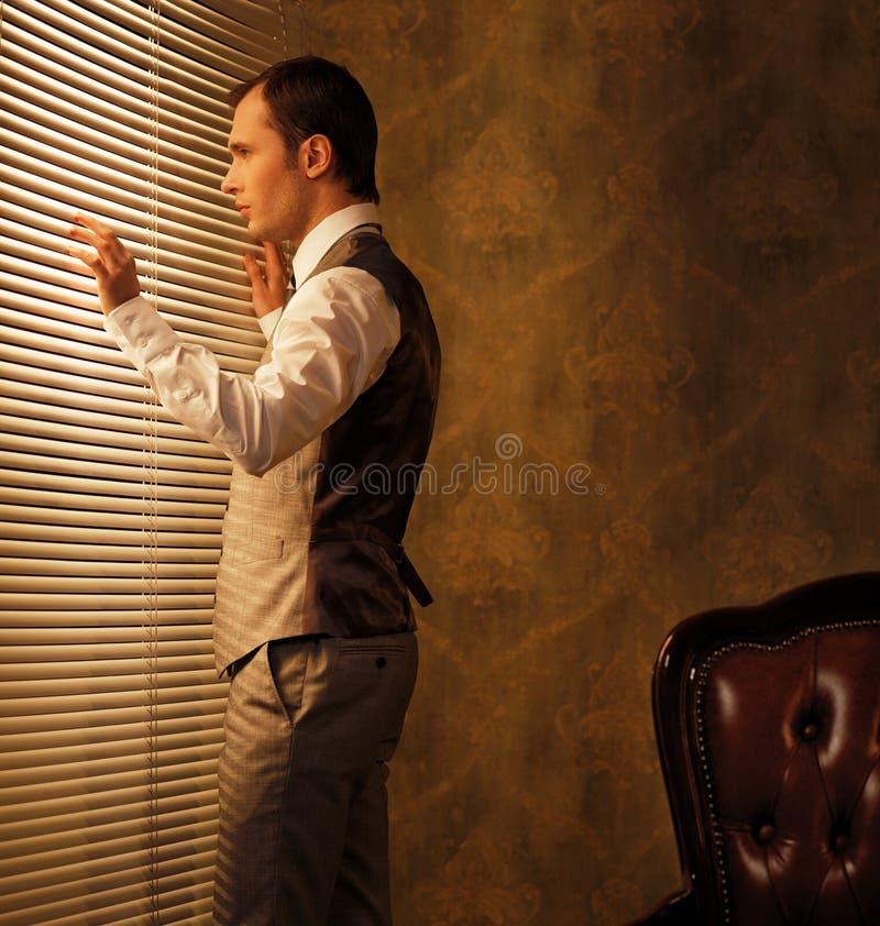 Homem no waistcoat perto do indicador imagens de stock