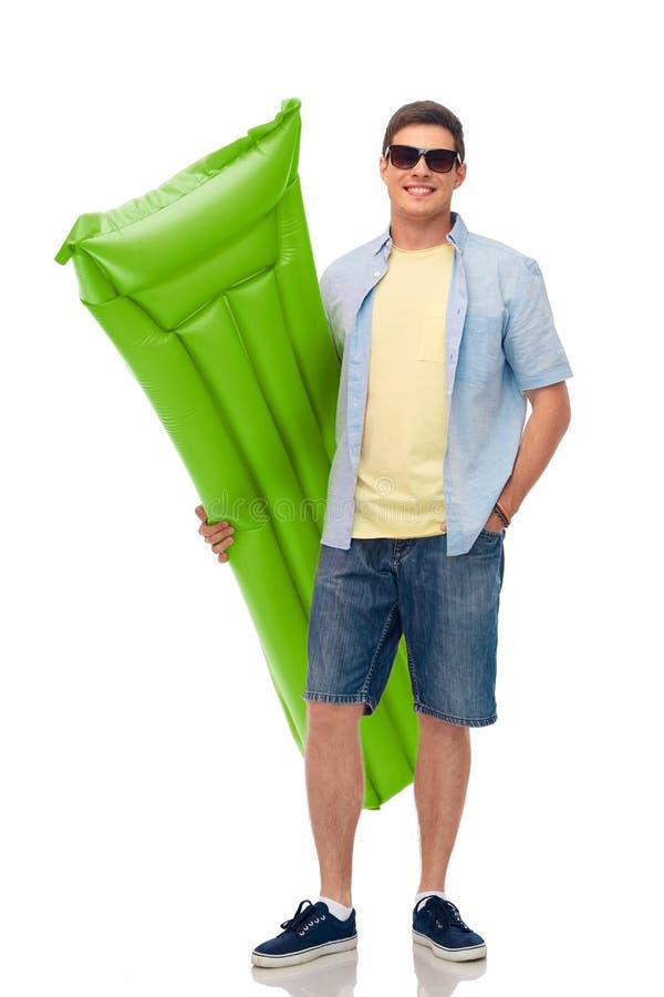 Homem nos óculos de sol com o colchão inflável da associação foto de stock royalty free