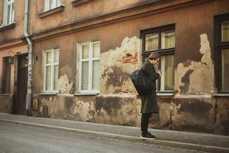 Homem nos cigarros de fumo da rua velha, em um revestimento longo O homem oferece amizade a um cigarro na cidade Um homem como de fotografia de stock royalty free