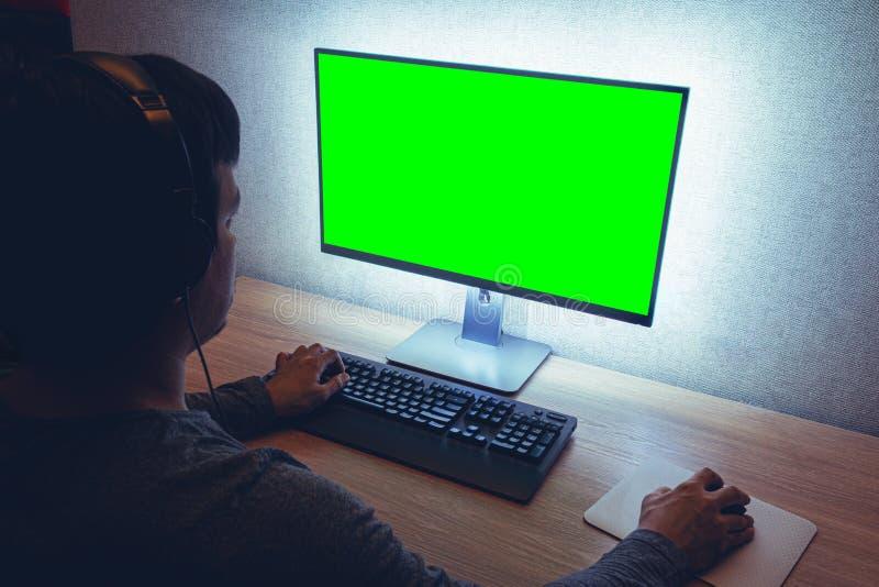 Homem nos fones de ouvido se senta na frente do monitor em sala escura foto de stock royalty free