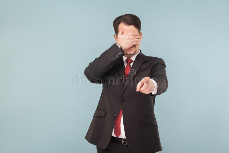 Homem nos olhos fechados do terno e no dedo apontar na câmera foto de stock