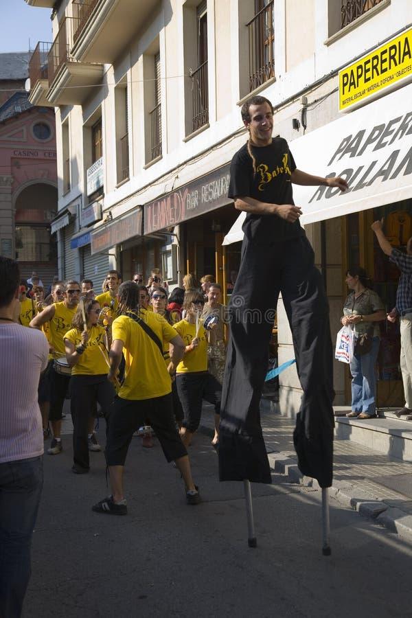 Homem nos pernas de pau e na banda que fazem sua maneira abaixo das ruas de Puigcerda, Girona, Catalunha, Espanha, Europa fotografia de stock