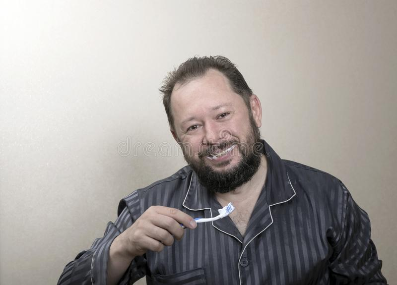 Homem nos pijamas que escovam seus dentes com uma escova de dentes fotografia de stock