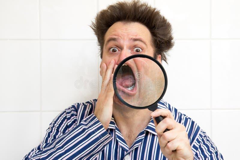 Homem nos pijamas que olha sua cara fotografia de stock