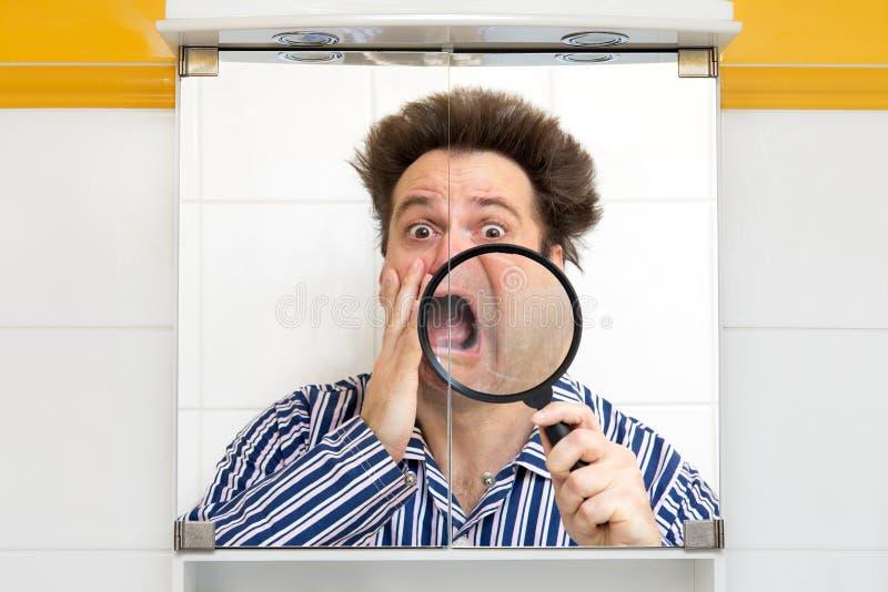 Homem nos pijamas que olha sua cara fotos de stock