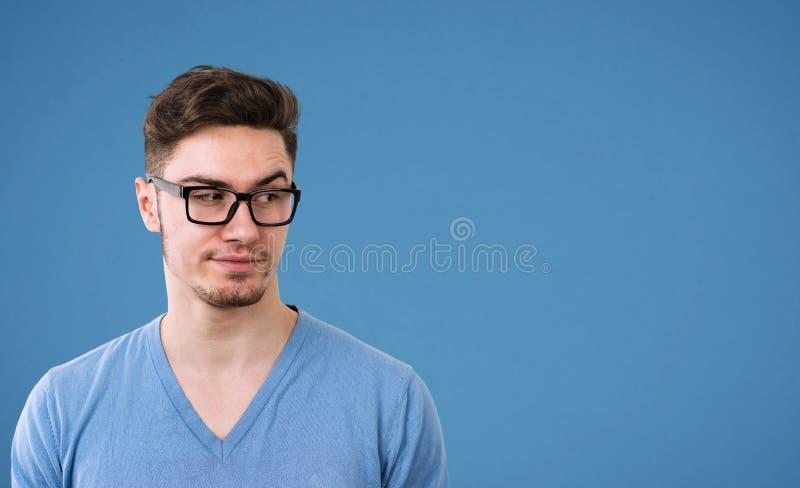 Homem nos vidros com olhar cético, sobrancelha dos aumentos na confusão foto de stock royalty free