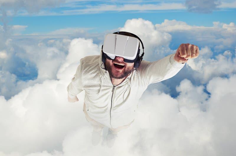 Homem nos vidros da realidade virtual que voam entre nuvens imagens de stock royalty free