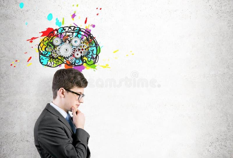 Homem nos vidros e cérebro com engrenagens fotografia de stock