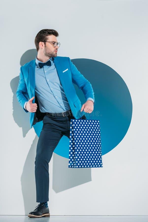 homem novo à moda considerável com o saco de compras que olha ausente ao pisar através do furo fotografia de stock royalty free