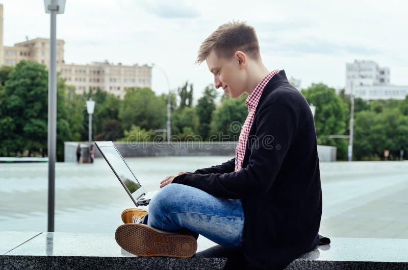 Homem novo à moda no revestimento e nas calças de brim que sentam-se e que datilografam no ar livre do laptop, vista lateral Tecn fotografia de stock royalty free