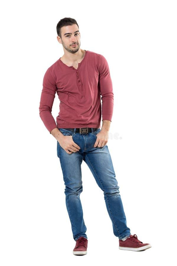 Homem novo à moda ocasional considerável com os polegares em uns bolsos que olham a câmera fotografia de stock royalty free