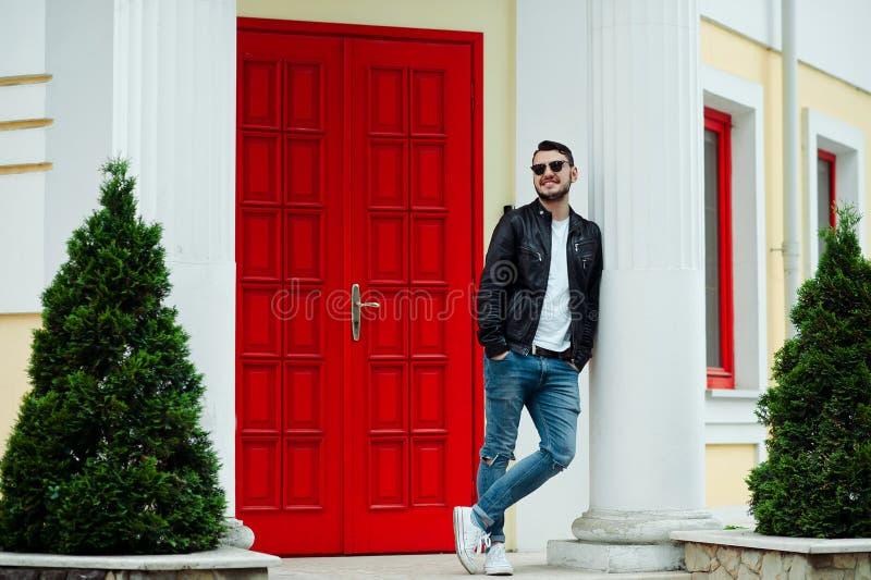 Homem novo ? moda que veste o casaco de cabedal, cal?as de brim ? moda e os ?culos de sol levantando no fundo da porta vermelha n imagens de stock