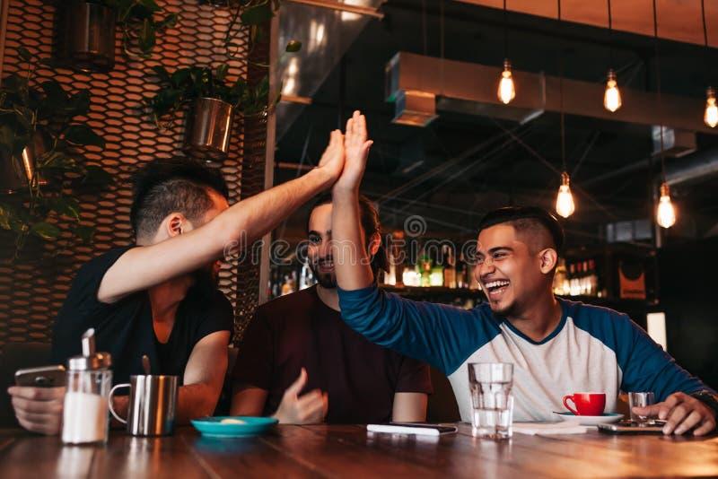 Homem novo árabe feliz que dá a elevação cinco a seu amigo Grupo de povos da raça misturada que têm o divertimento na barra da sa fotografia de stock royalty free