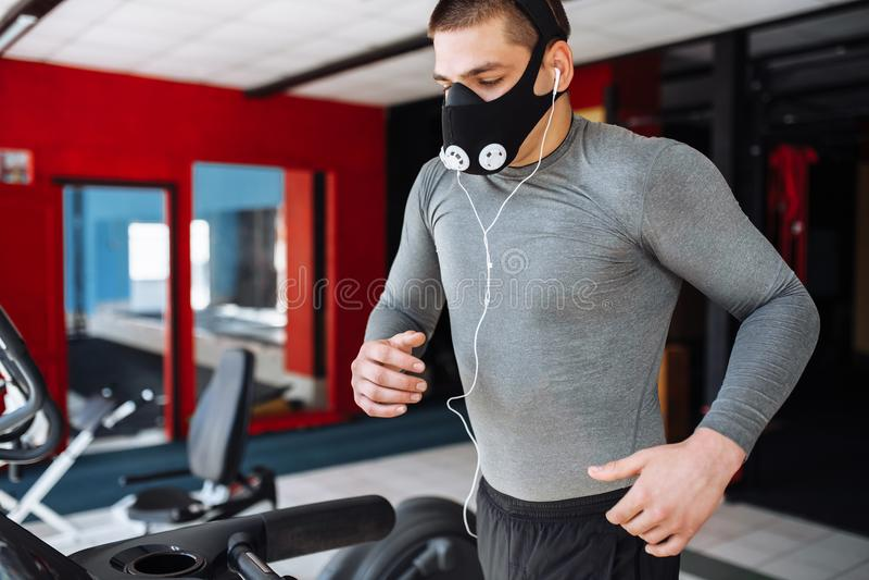 Homem novo acima bombeado bonito, contratado nos esportes, na máscara do treinamento para respirar na escada rolante, treinamento foto de stock royalty free