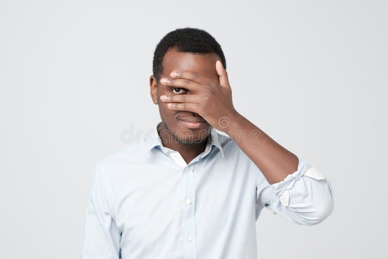 Homem novo africano agradável atrativo que fecha seus olhos com palma e que olha a tentativa foto de stock