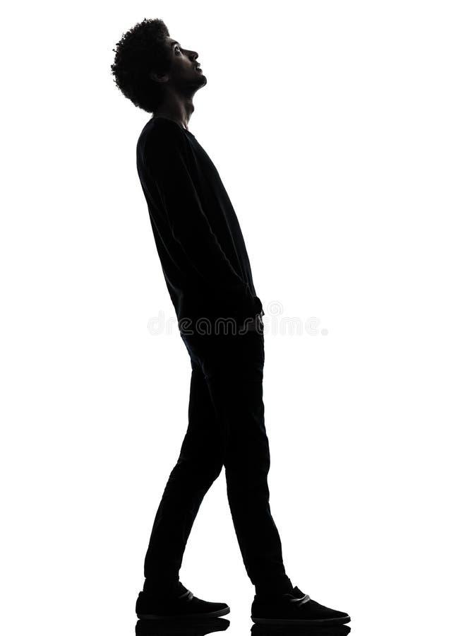 Homem novo africano considerável que está de vista acima o silhouet da surpresa imagens de stock
