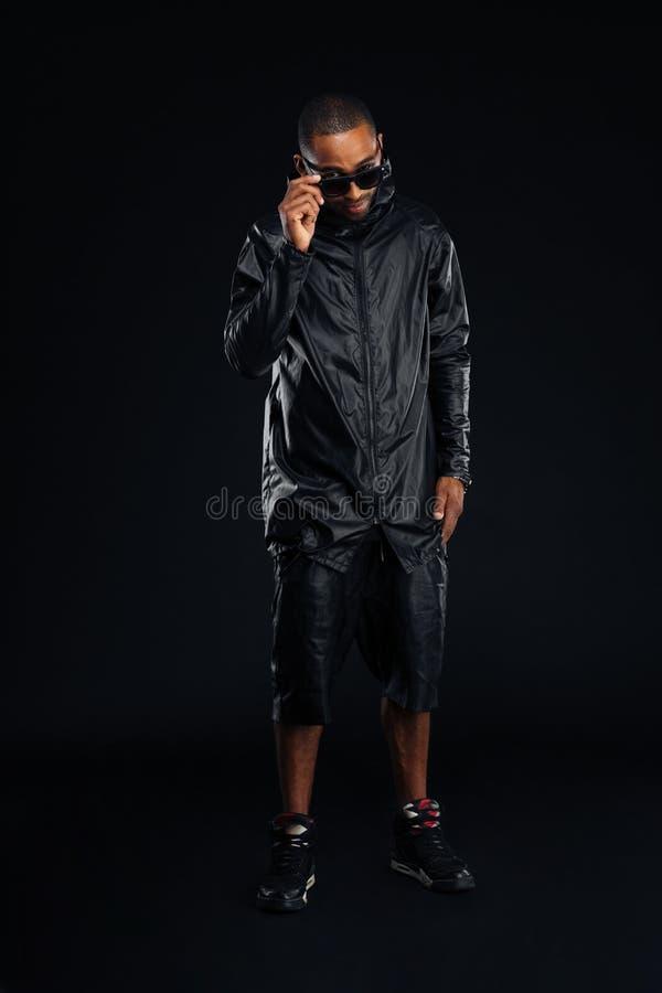 Homem novo afro-americano à moda de sorriso no levantamento dos óculos de sol foto de stock