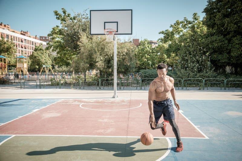 Homem novo afro-americano que joga o basquetebol da rua no parque foto de stock