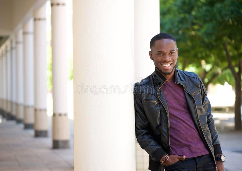 Homem novo afro-americano que sorri no casaco de cabedal preto imagem de stock