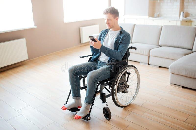 Homem novo agrad?vel com inclus?o e inabilidade Assento na cadeira de rodas Guardando o telefone nas m?os e para olh?-lo Luz do d foto de stock royalty free