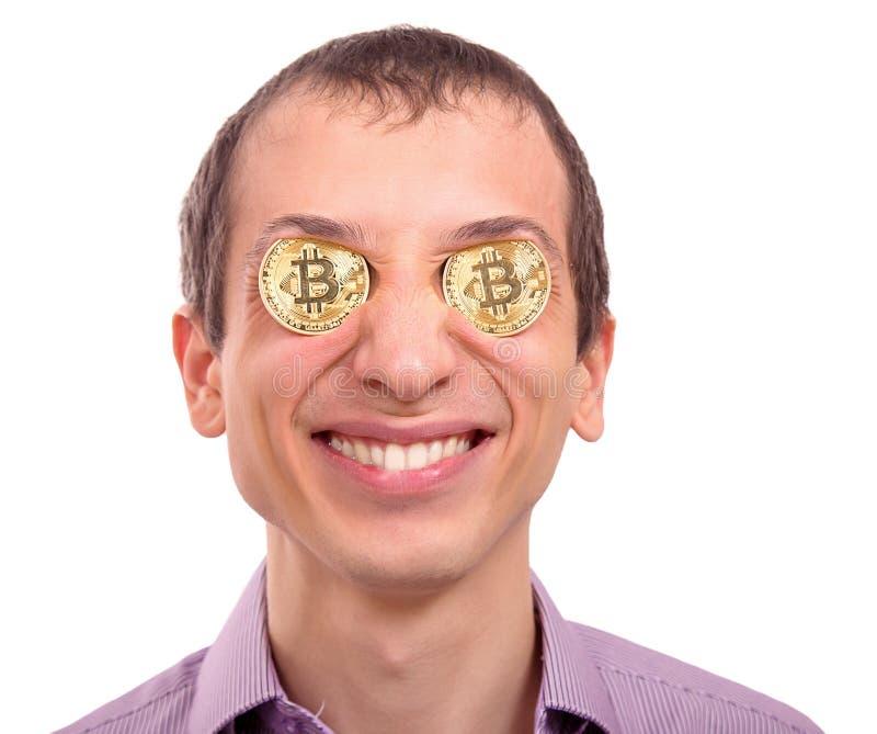 Homem novo alegre com bitcoin do ouro nos olhos fotografia de stock royalty free