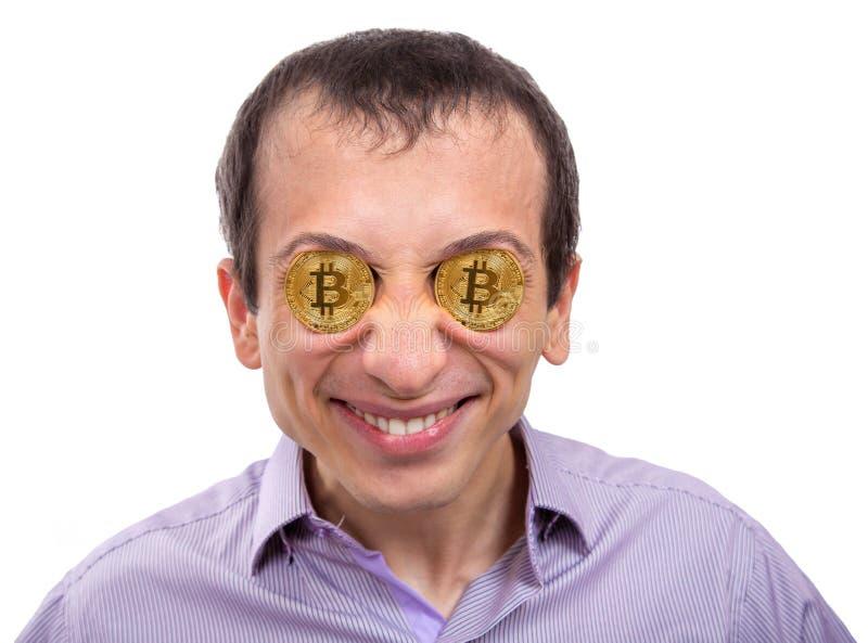 Homem novo alegre com bitcoin do ouro nos olhos fotografia de stock