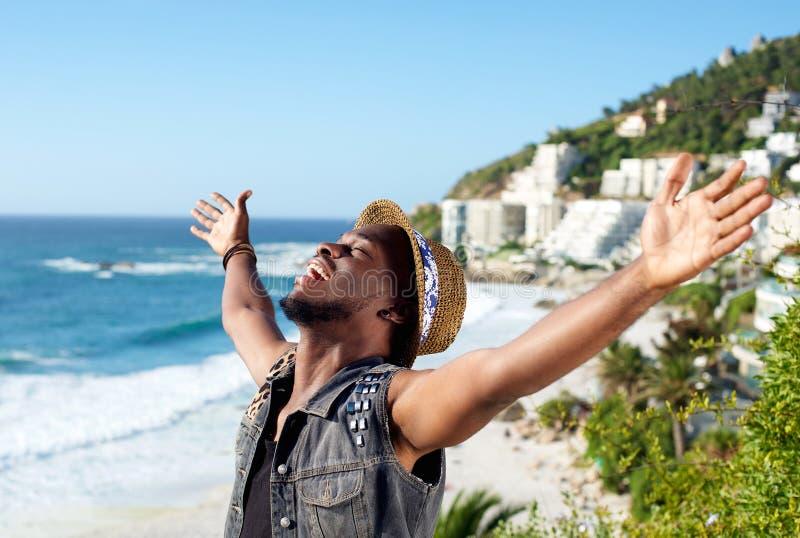 Homem novo alegre com a propagação dos braços aberta na praia imagens de stock
