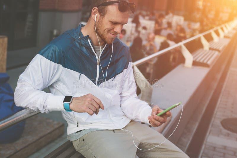 Homem novo alegre com relógios espertos e o telefone celular que sentam-se fora fotos de stock