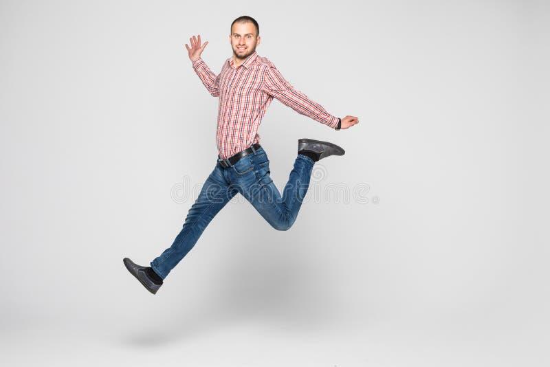 Homem novo alegre entusiasmado feliz que salta e que comemora o sucesso isolado em um fundo branco fotos de stock royalty free