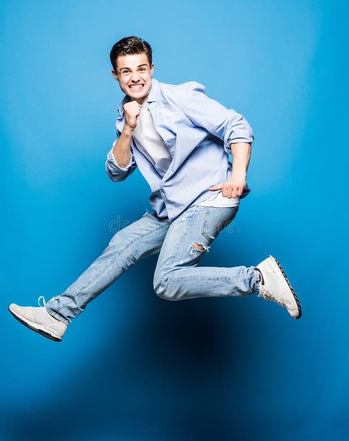 Homem novo alegre entusiasmado feliz que salta e que comemora o sucesso isolado no fundo azul imagens de stock