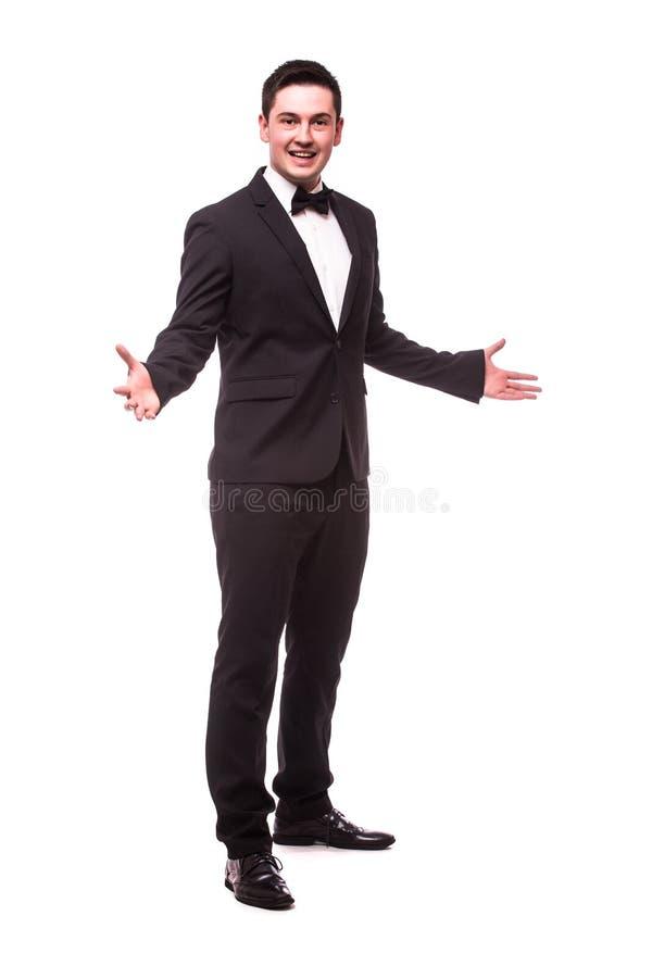 Homem novo alegre no sinal bem-vindo e no sorriso do terno ao estar fotografia de stock