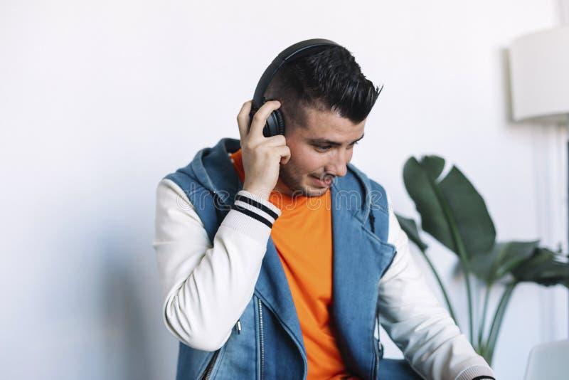 Homem novo alegre nos fones de ouvido que escuta a m?sica ao sentar-se em seu lugar de funcionamento fotografia de stock royalty free