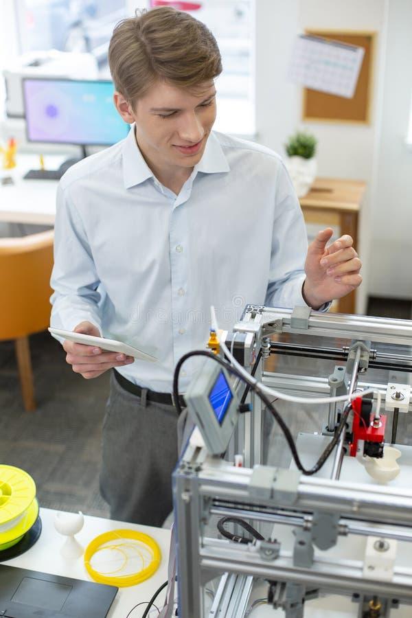 Homem novo alegre que pratica em usar a impressora 3D fotos de stock royalty free
