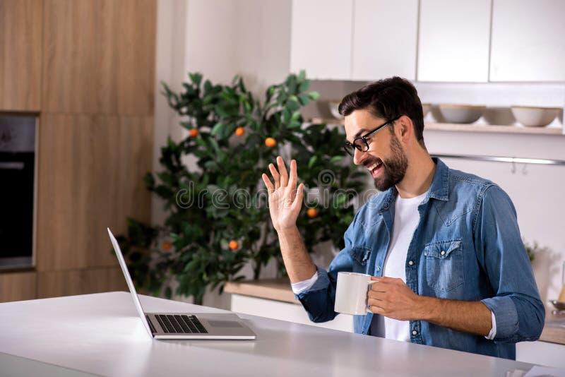 Homem novo alegre que senta-se na cozinha imagens de stock