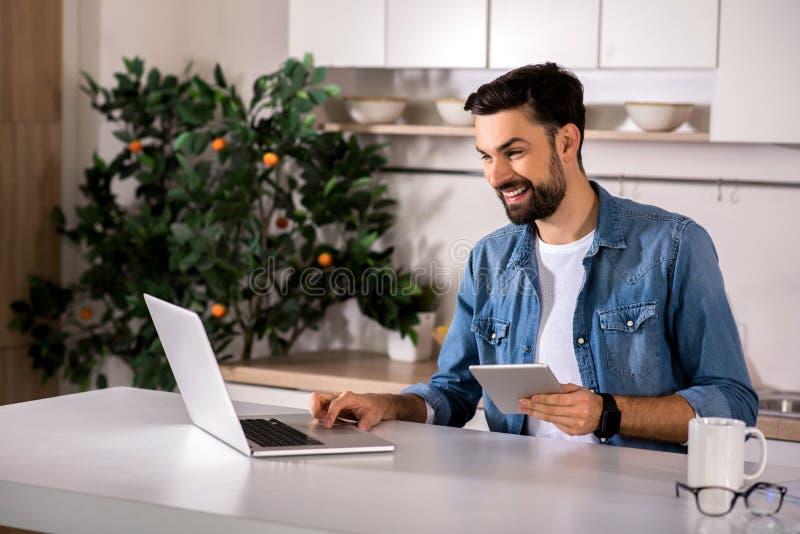 Homem novo alegre que usa seu portátil imagens de stock royalty free